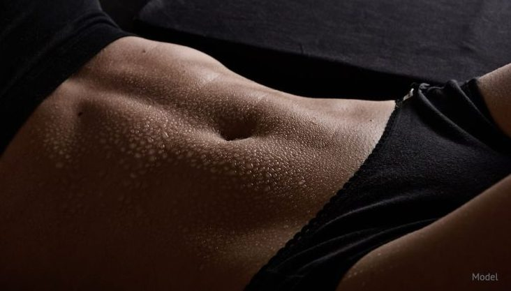 Flat stomach that tummy tuck can achieve with dark lighting