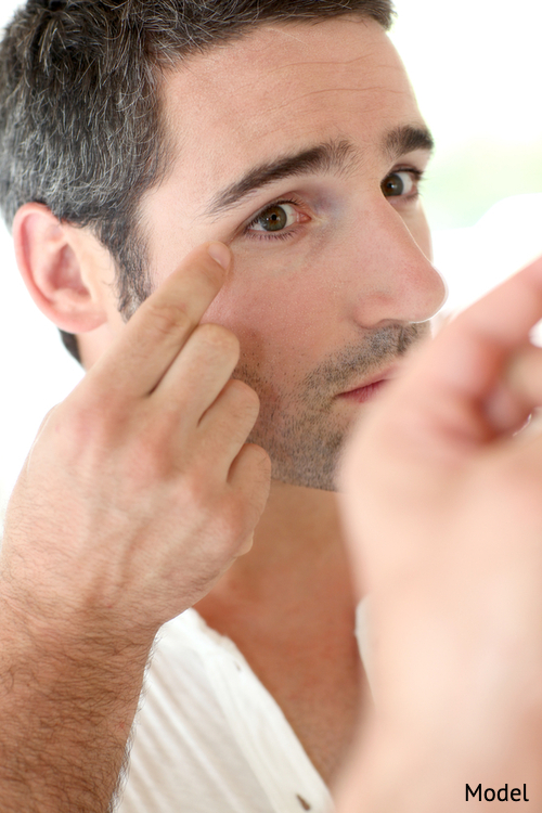 Man looking at wrinkles in mirror, considering a plastic surgery procedure.